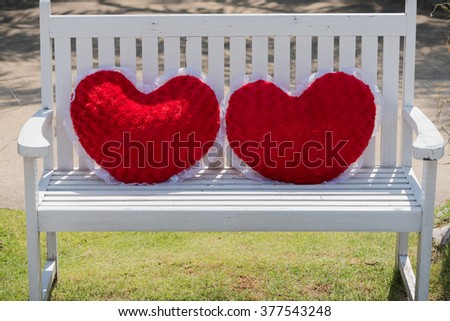 Heart Shaped Pillow Cushions Put On The white Chair - stock photo