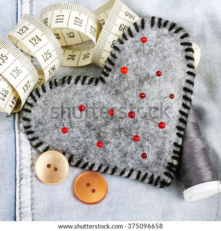 Heart shaped pincushion and tailor accessories - stock photo