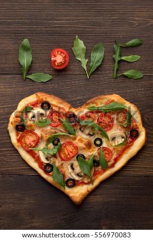 Tim bánh pizza hình cho ngày Valentine trên nền gỗ mộc mạc tối với chữ tình yêu.  Top xem, không gian sao chép.