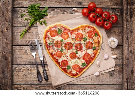 Heart shaped pizza margherita love concept for Valentines Day with mozzarella, tomatoes, parsley and garlic on vintage wooden table background. - stock photo