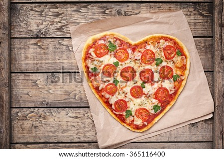 Heart shaped pizza margherita with tomatoes and mozzarella for Valentines Day on vintage wooden background. Food concept of romantic love. - stock photo