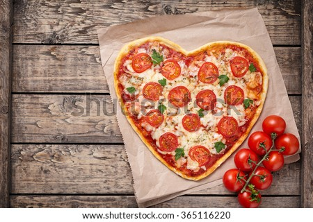 Heart shaped pizza margherita with tomatoes and mozzarella vegetarian meal on vintage wooden table background. Food concept of romantic love for Valentines Day. - stock photo
