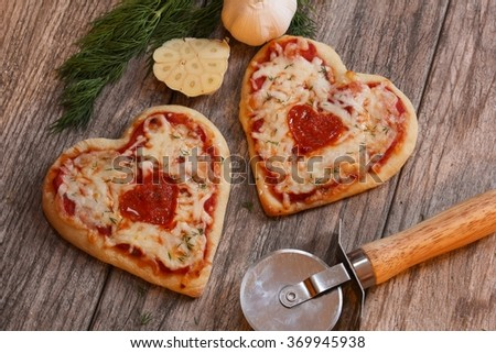 Heart shaped pizza on wooden background, top down view - stock photo