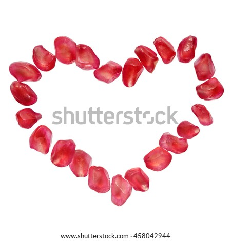 Heart shaped pomegranate seeds isolated on white. Love, passion symbol, super food concept