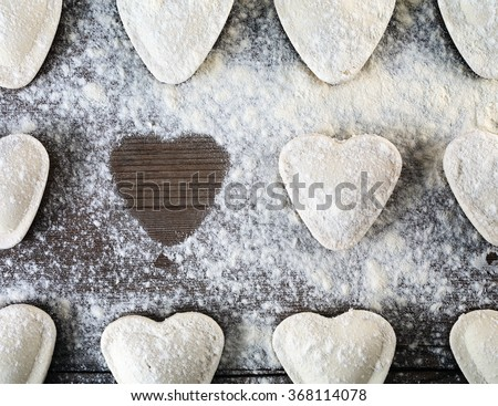 Heart shaped ravioli sprinkle with flour, on wooden background. Cooking dumplings. Top view. Uncooked ravioli hearts - stock photo