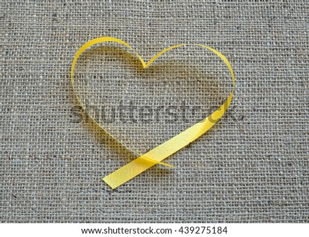 Heart shaped ribbon on linen background - stock photo