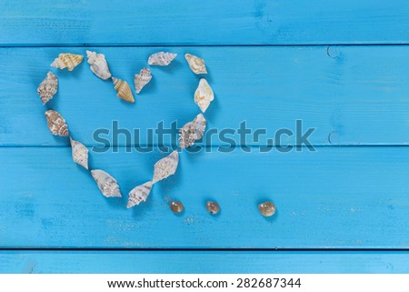 Heart shaped sea shells on a blue rustic background.