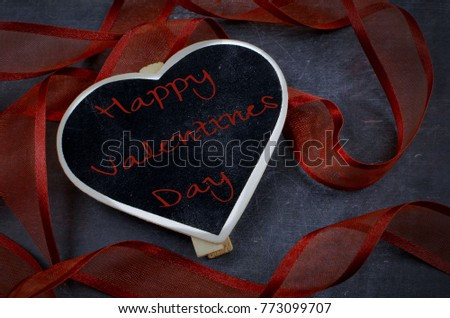 Heart shaped small slate blackboard on slate background. Silky and sheer red ribbon winding around. Valentine message added. Vignette added.