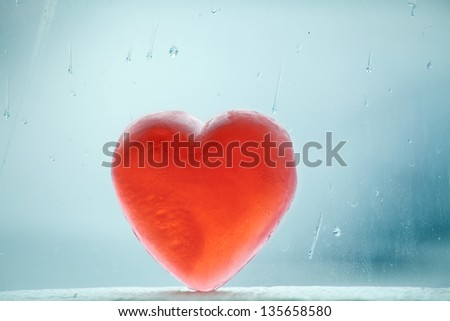 Heart shaped soap leaning on a window covered with rain drops on a winter day. - stock photo