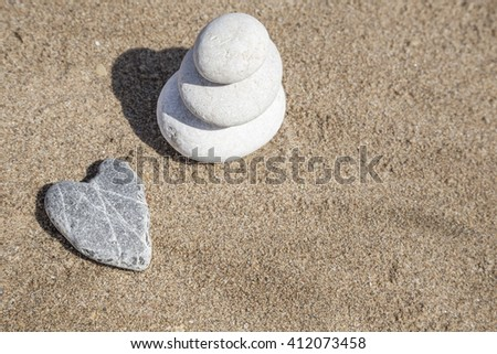 heart shaped stone and stack of pebbles on balance on sand - stock photo
