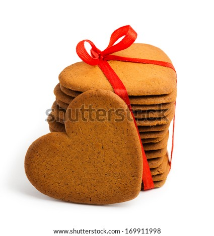 Heart shaped sugar cookie tied with red ribbon on white - stock photo