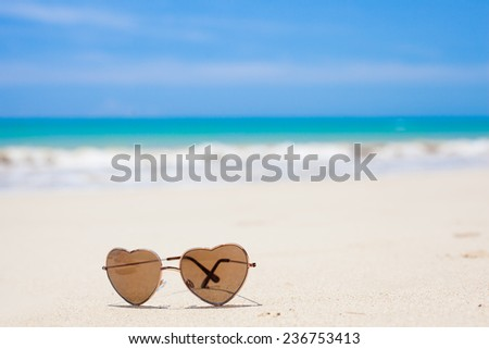 heart shaped sunglasses lying on tropical sand beach. party