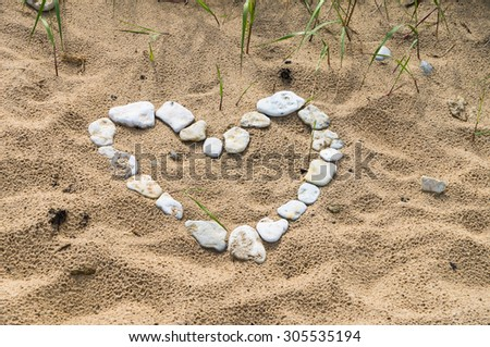 Heart shaped symbol made of small stones on a wild beach