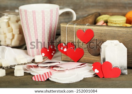 Heart shaped teabag tags, macaroons and cup of tea on wooden background - stock photo