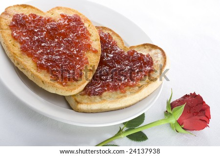 Heart shaped toast, spread with butter and Strawberry jam, on a plate with a red rose placed on the white table cloth beside it. - stock photo