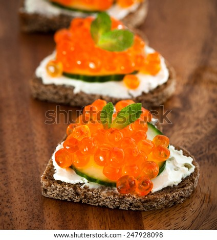Heart shaped toasts appetizer with red caviar - stock photo