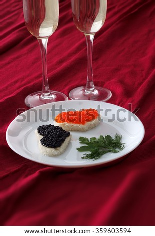 Heart shaped toasts with red and black caviar and two glasses of champagne on white plate on red drapery, close up - stock photo