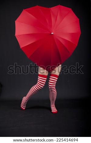 Heart Shaped Umbrella With Female Legs - stock photo
