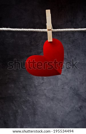Heart shaped Valentine's Day card with copy space attached to a rope with clothes pins. Romance, love and affection concept. - stock photo