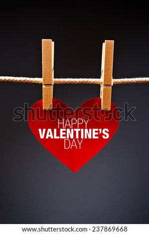 Heart shaped Valentine's Day card with message attached to a rope with clothes pins. Romance, love and affection concept. - stock photo