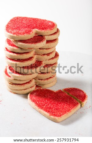 heart shaped Valentine's Day cookies, with broken heart over marble board, isolated on white background, close up, macro, selective focus, vertical - stock photo