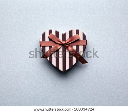 Heart shaped Valentines Day gift box on gray textured paper background. - stock photo