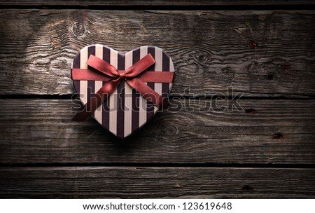 Heart shaped Valentines Day gift box on old wood. Vintage holiday background. - stock photo