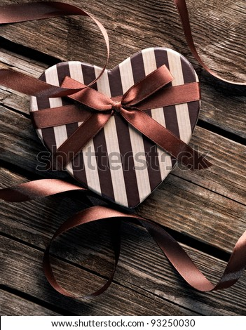 Heart shaped Valentines Day gift box with curved ribbon on old wood. Vintage holiday background. - stock photo