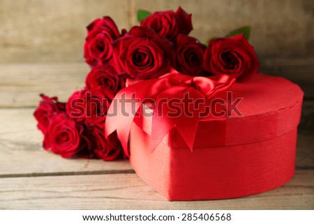 Heart shaped Valentines Day gift box with red roses on old wooden table - stock photo