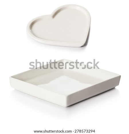 Heart shaped white porcelain soap dish and square white ceramic bathroom tray over white background. - stock photo