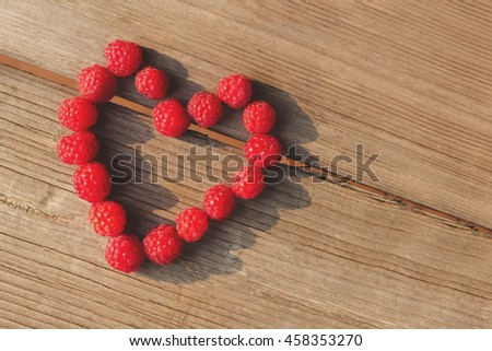 Heart sweet red raspberries on wooden table - stock photo
