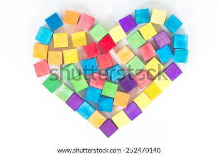 Heart symbol made of colourful wooden toy isolated over the white background - stock photo