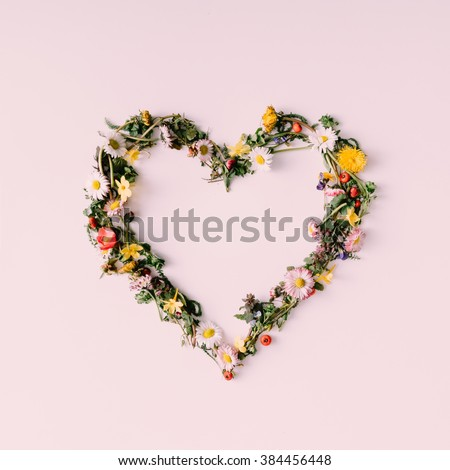 Heart symbol made of flovers and leaves on white background.