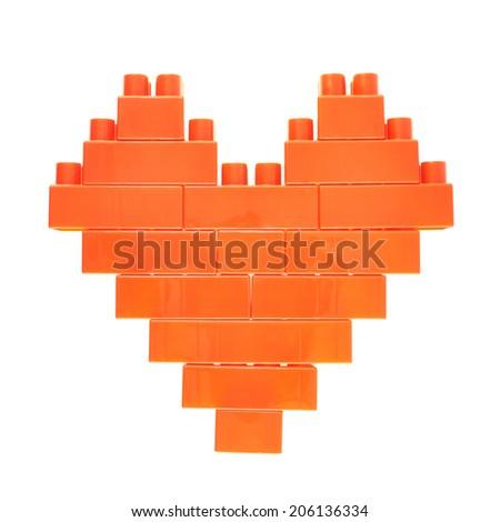 Heart symbol made of orange plastic toy construction bricks isolated over the white background - stock photo