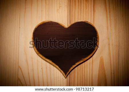 Heart symbol made of wood in front of a wooden background.