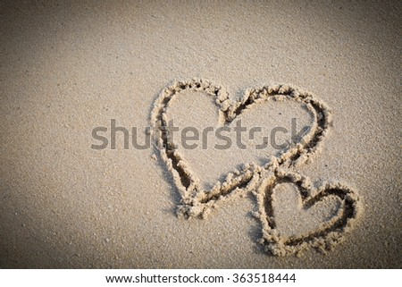 Heart twice wrote on beach. - stock photo