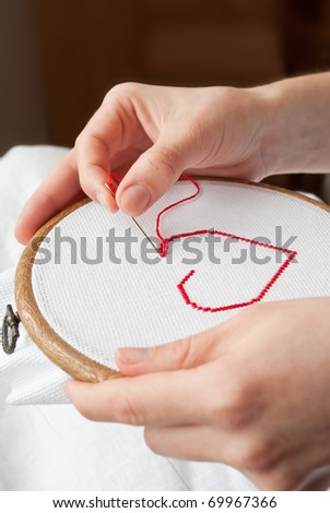 heart (valentine) on canvas being embroidered by female hands - stock photo