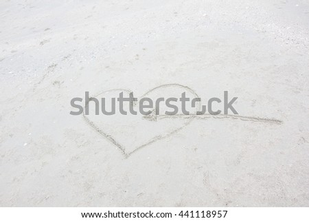 heart with arrow drawn in the sand on the beach