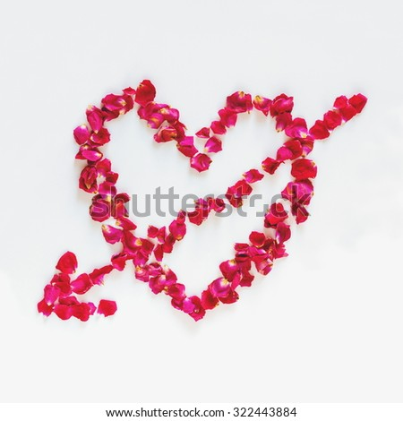 Heart with arrow made of rose petals - stock photo