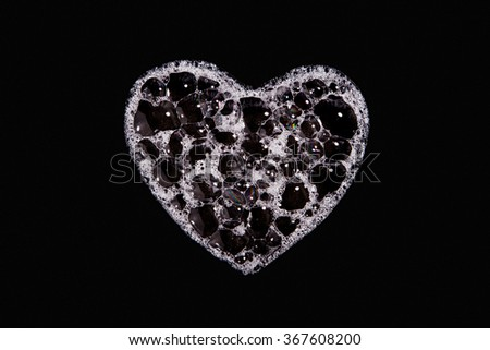 Heart with bubbles on black background - stock photo