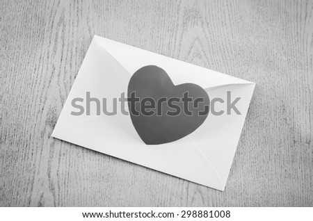 heart with envelope on wooden background black and white color tone style - stock photo