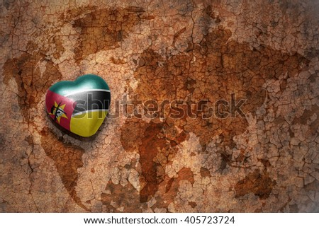 heart with national flag of mozambique on a vintage world map crack paper background. concept - stock photo