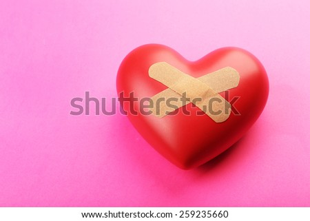 Heart with plaster on colorful background - stock photo