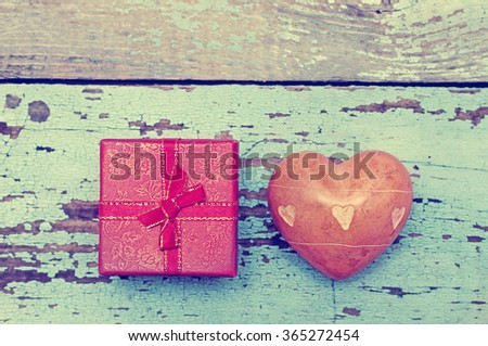 Heart with stones and small gift box with a bow on a wooden background. Greeting card for lovers, friendship or valentine's day. - stock photo