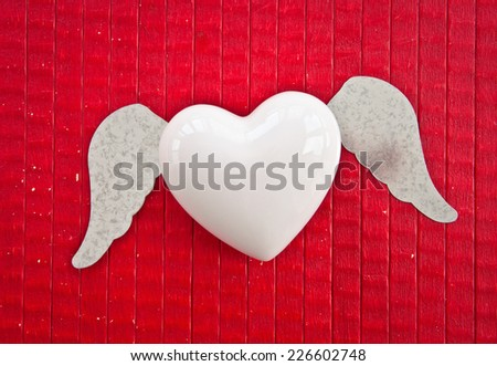 Heart with wings on red rustic wooden background - stock photo