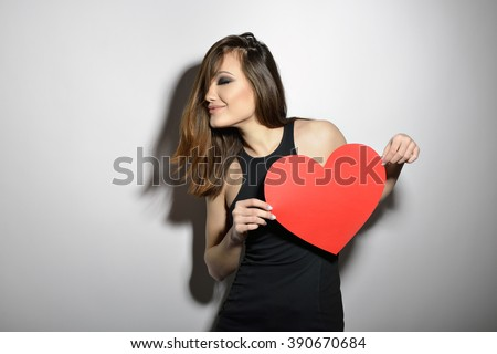 Heartbreaker. Temptress. Seductive woman. Portrait of amazing young fashion woman posing at studio with red heart. Love. Valentine's day.  - stock photo