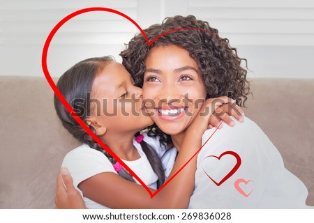 Hearts against pretty mother sitting on the couch with her daughter kissing her cheek - stock photo