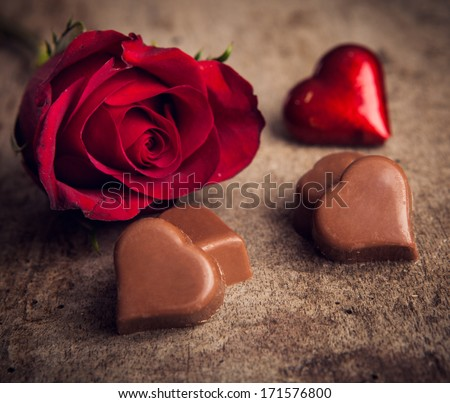 hearts, chocolate and red roses on wooden board, Valentines Day background - stock photo