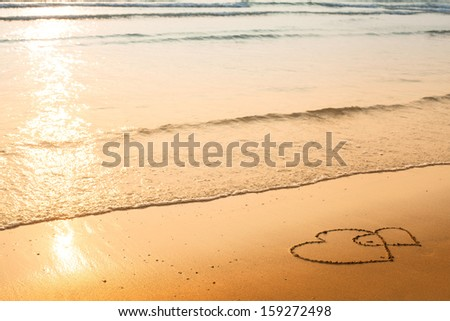 Hearts drawn on the sand of a beach, soft wave of the sea - stock photo