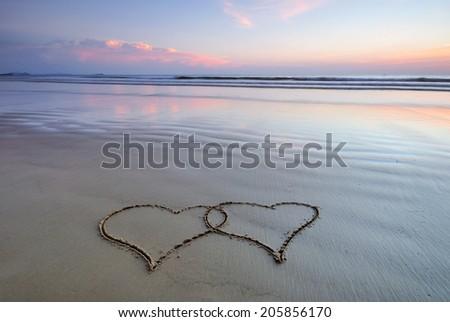 Hearts hand written on sand at sunset, love shape - stock photo
